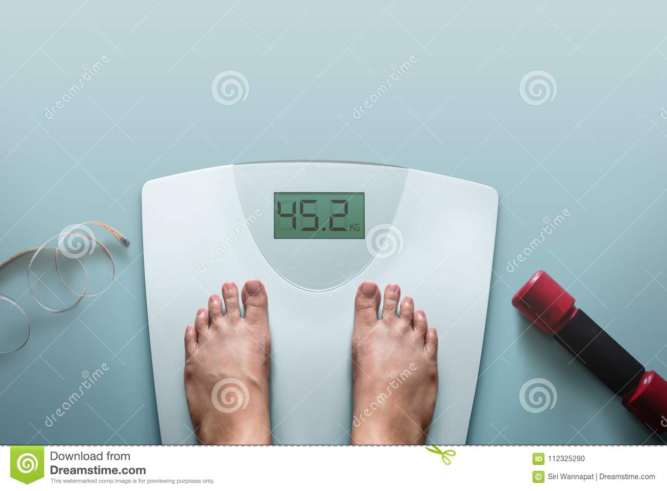 Exercising and Diet Concept, Woman Standing on Digital Weight Sc