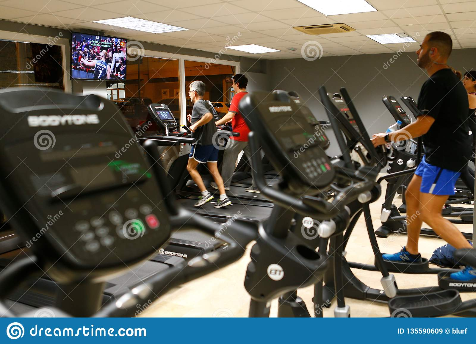 Exercising on gym fitness machines side view editorial stock image