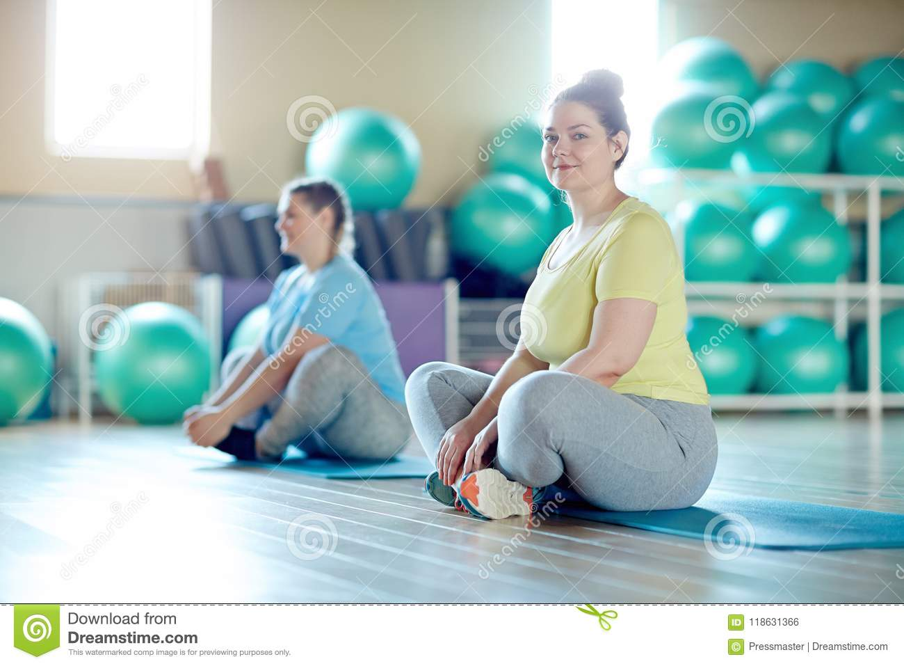 Young chubby cross-legged women and her groupmate in activewear sitting on  mats while exercising in fitness center