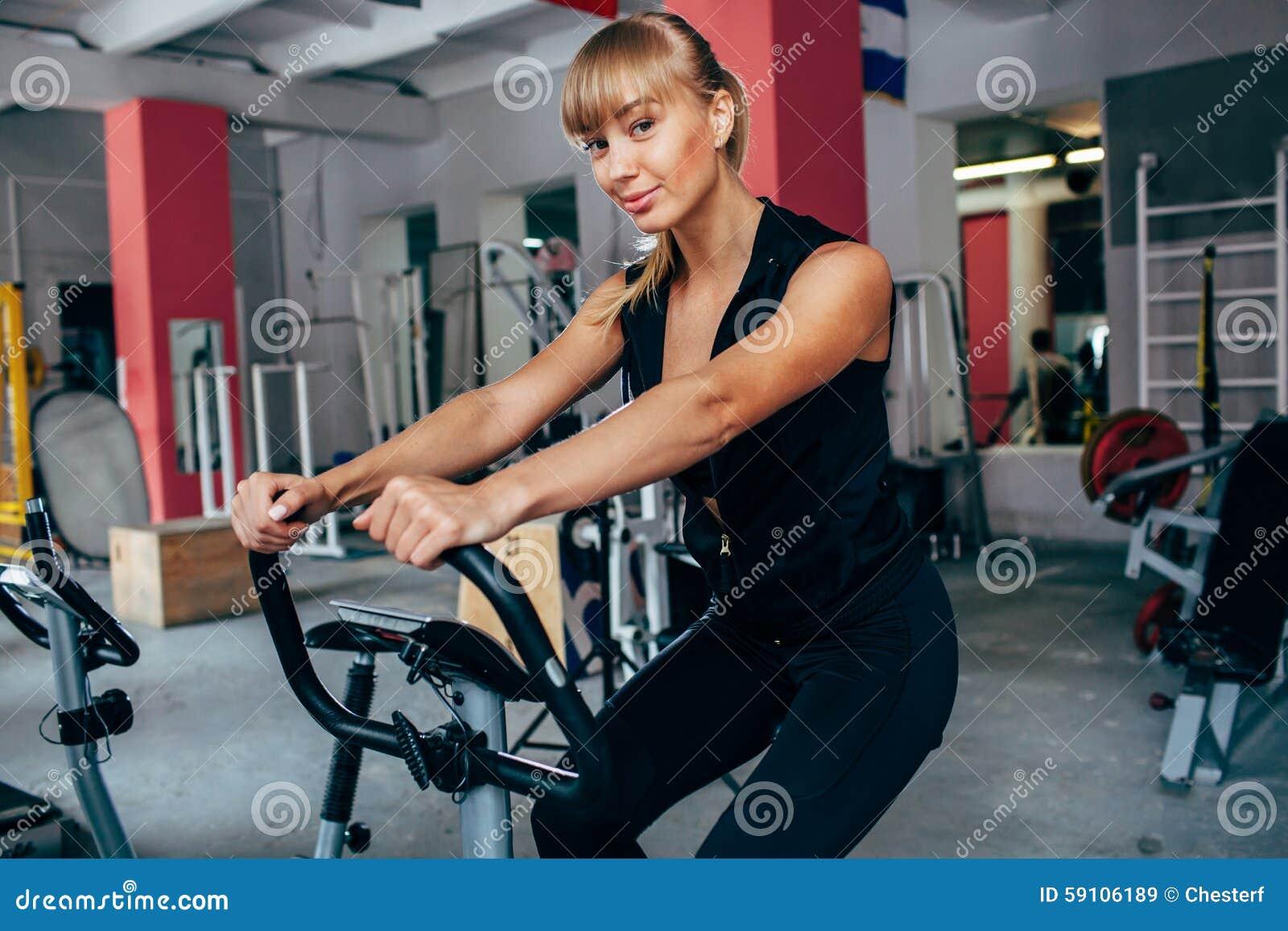 Exersizing的自行车的白肤金发的妇女