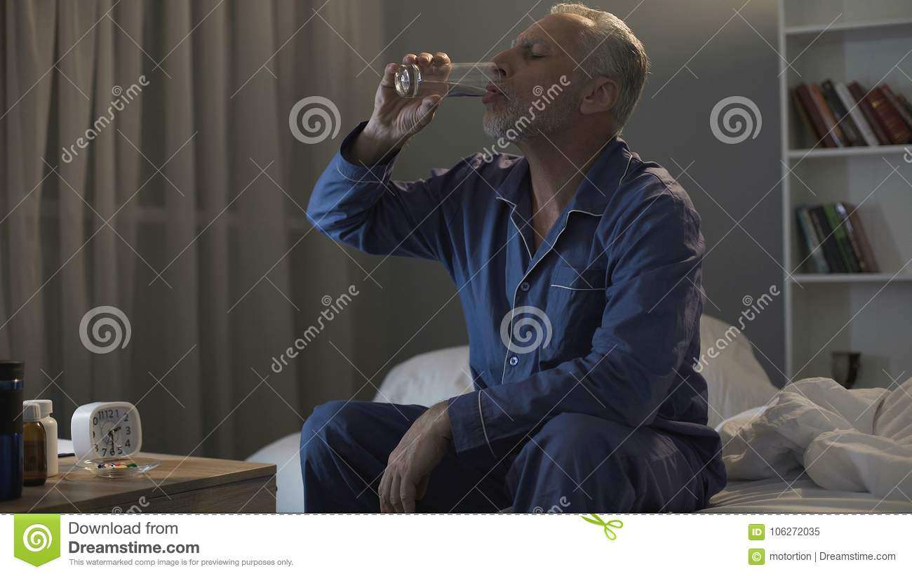 Exhausted Man In His 50s Sitting In Bed And Taking