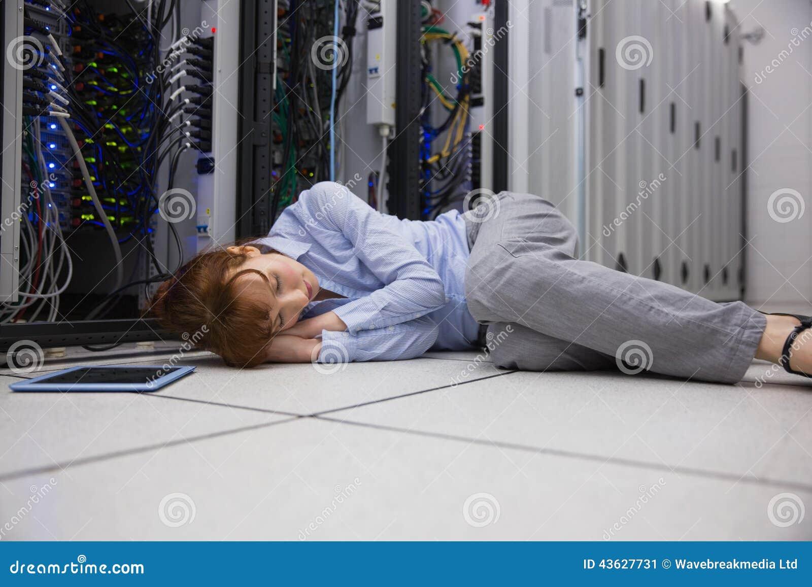 Exhausted technician sleeping on the floor stock photo for Is sleeping on the floor good