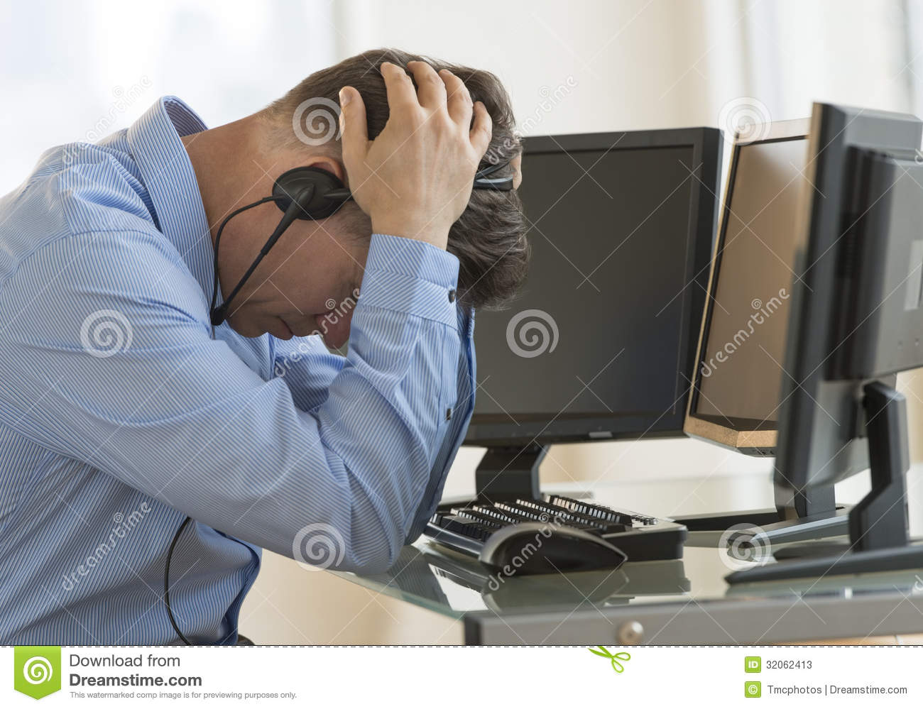Exhausted Trader With Head In Hands Leaning At Computer Desk Stock