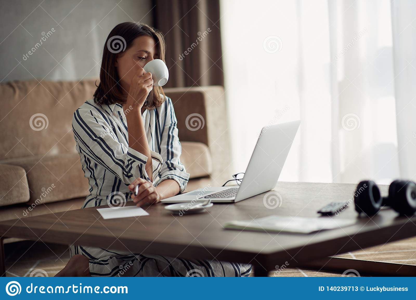 Exhausted woman working at home with a laptop and drinking coffee