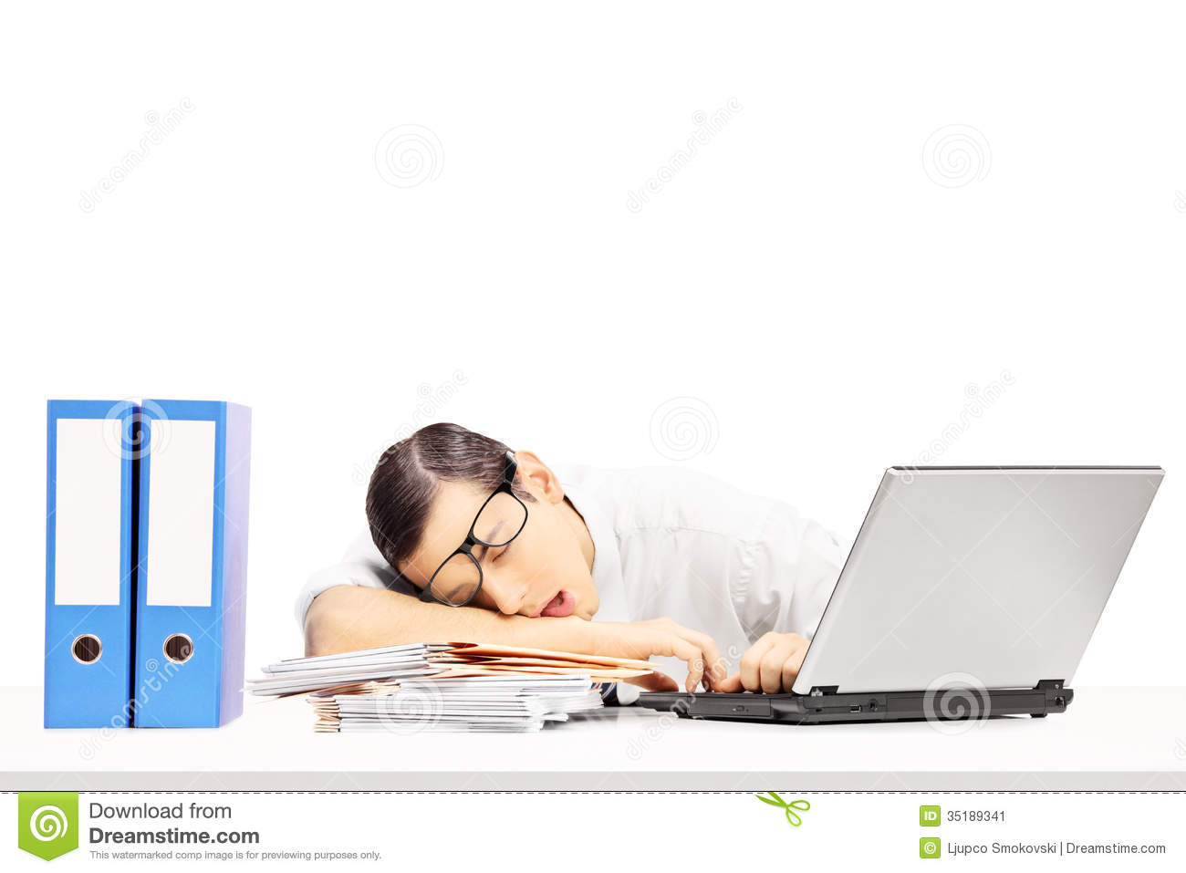 Exhausted Young Businessman Sleeping On A Desk At His