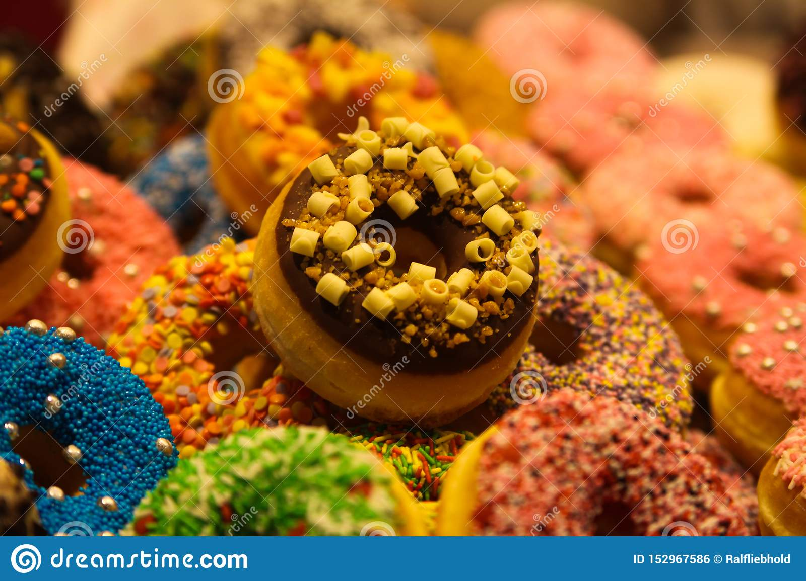 Exhibition of colorful donuts decorated with fancy crumbles in the market hall of Rotterdam, Netherlands