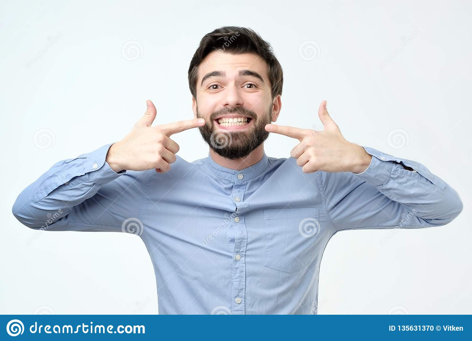 Exibição segura de sorriso do homem latino-americano e apontar com dentes e boca dos dedos