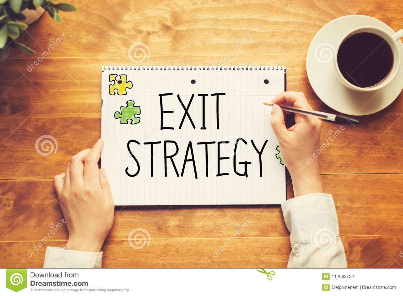 Exit Strategy text with a person holding a pen
