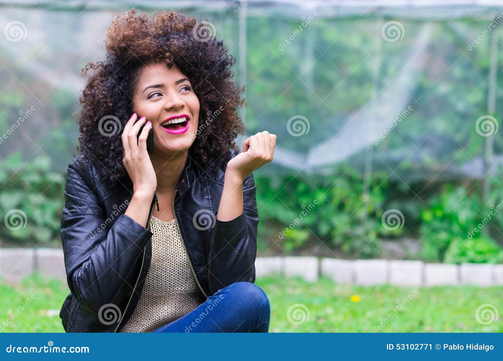 Exotisch mooi jong meisje die celtelefoon met behulp van