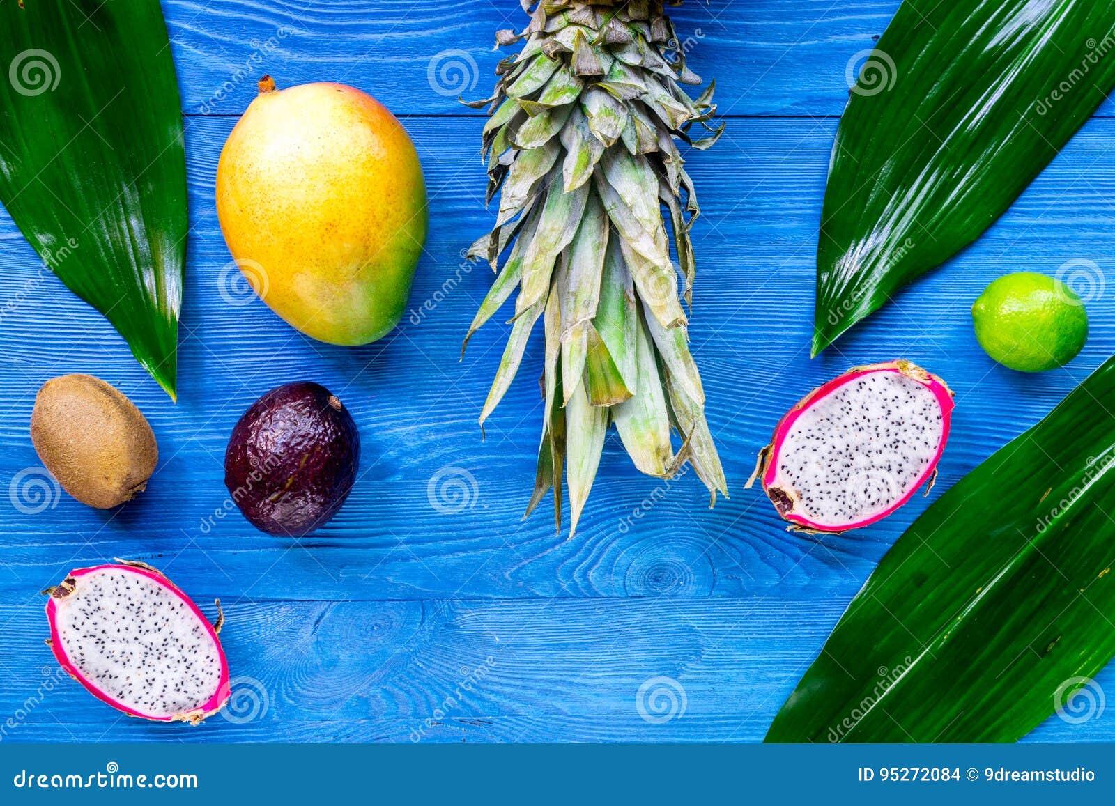 Exotiskt fruktmål Dragonfruit, mangosteen, mango, kiwi, limefrukt och ananas på blå träcopyspace för bästa sikt för bakgrund