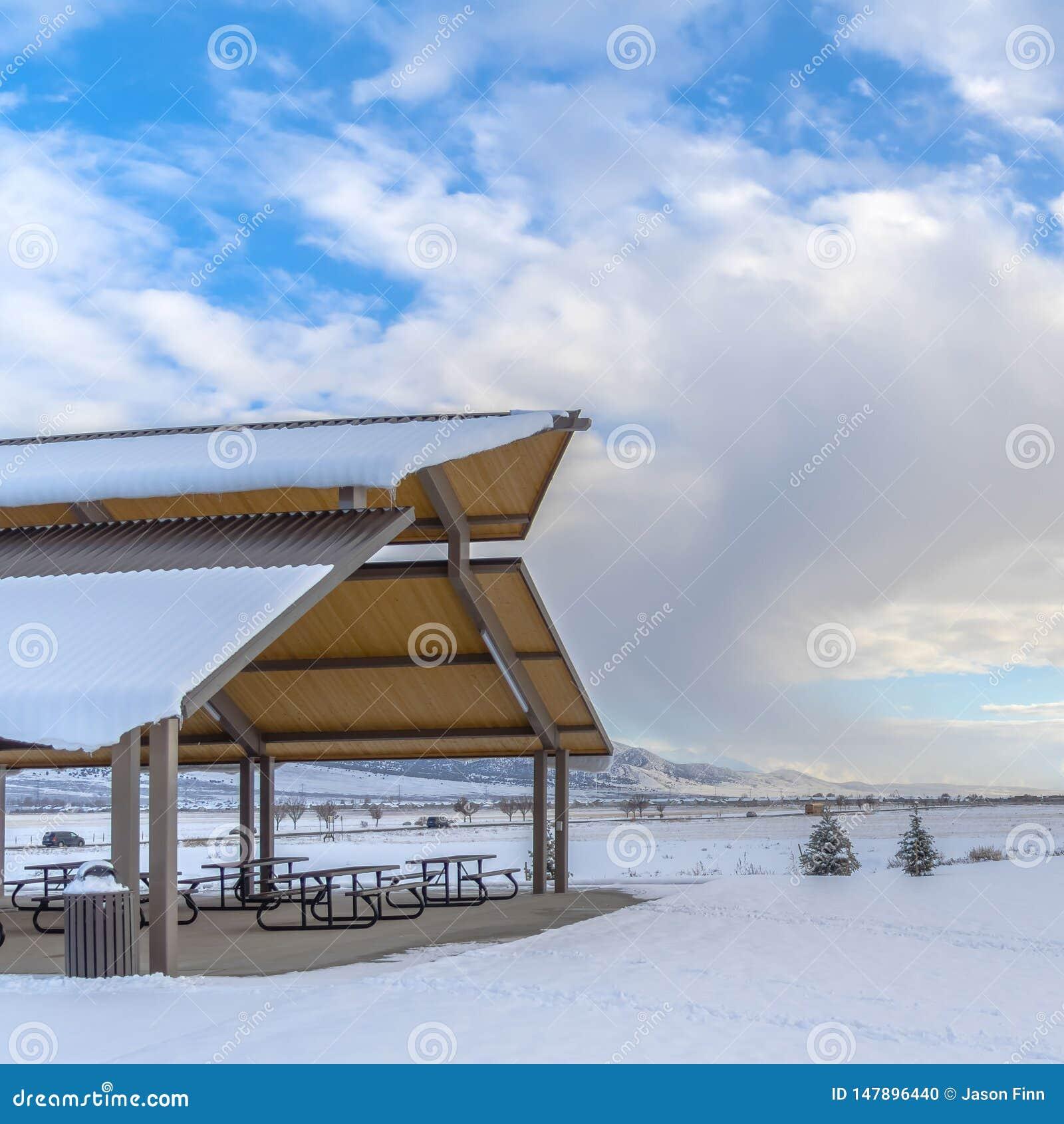 Expansivt landskap för klar fyrkant som filt med snö under en molnig blå himmel i vinter under