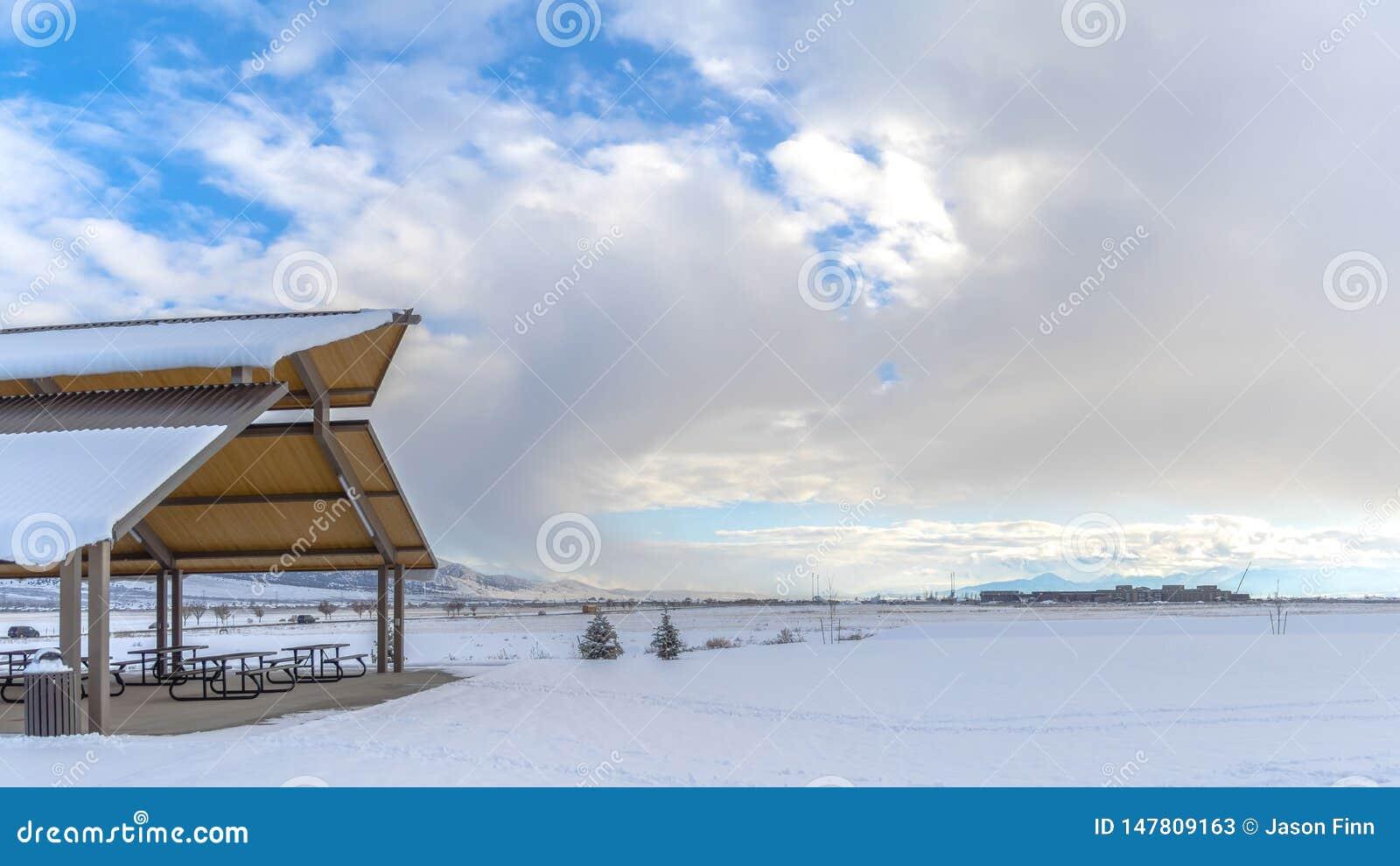 Expansivt landskap för panorama som filt med snö under en molnig blå himmel i vinter under