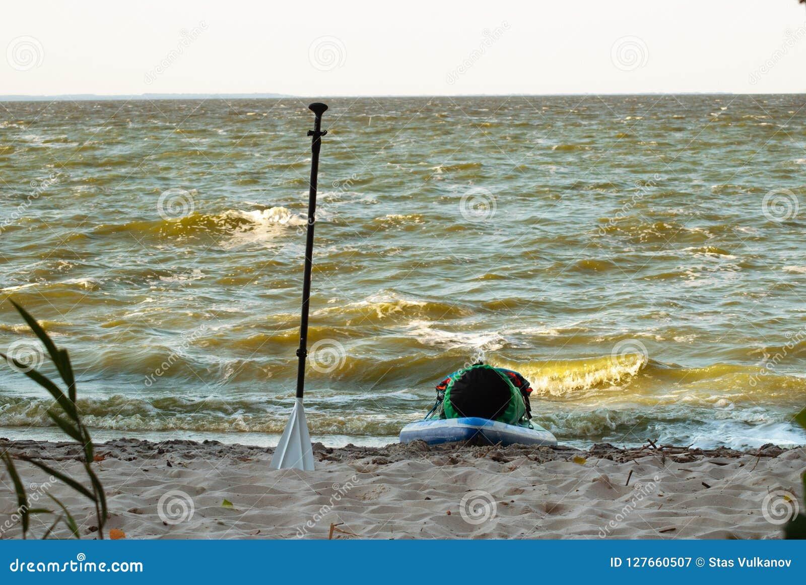 Expedition stehen oben paddleboard, ein Paddel und ein Sup Brett auf dem Ufer,