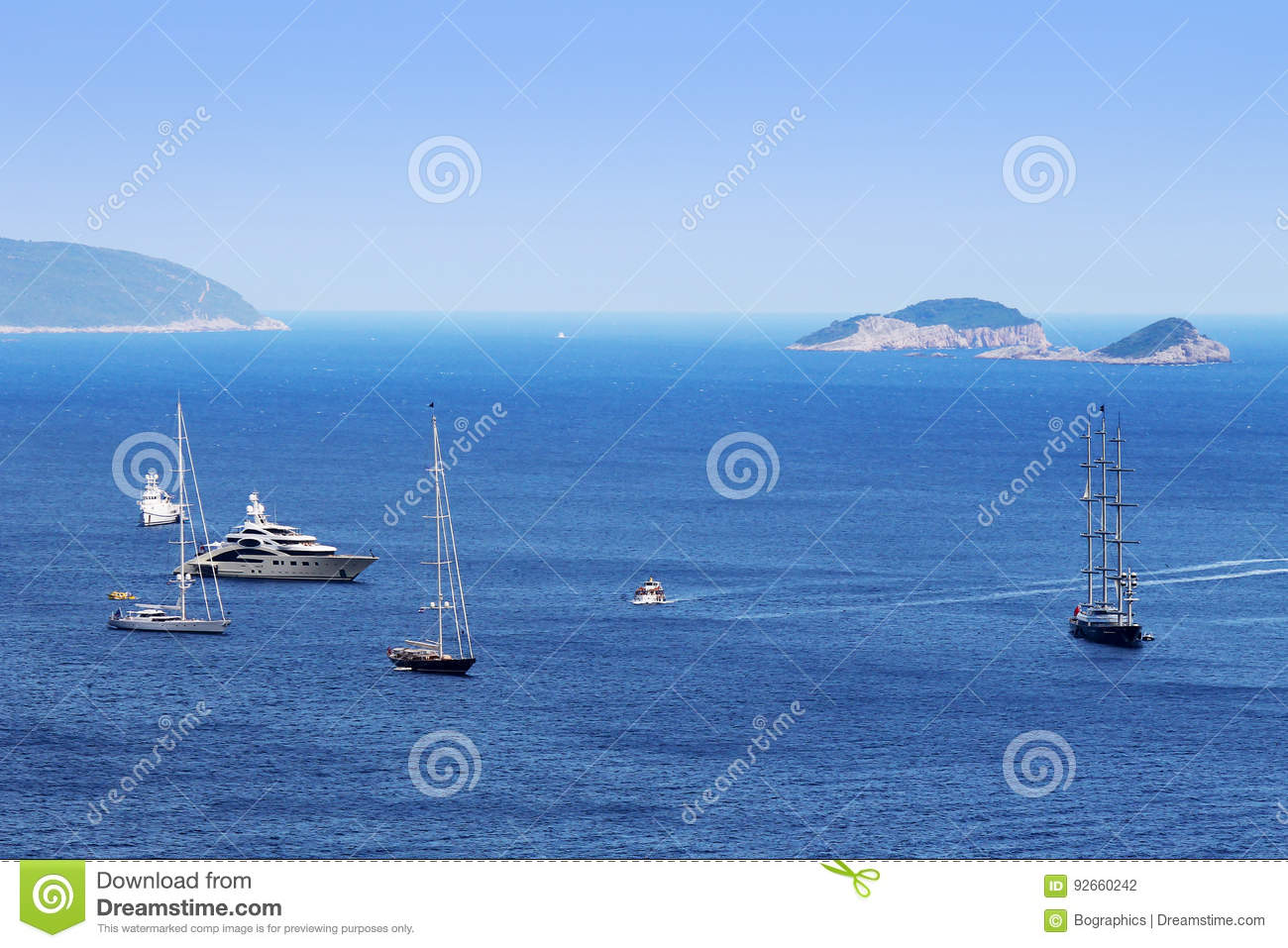 Expensive boats on large sea with island