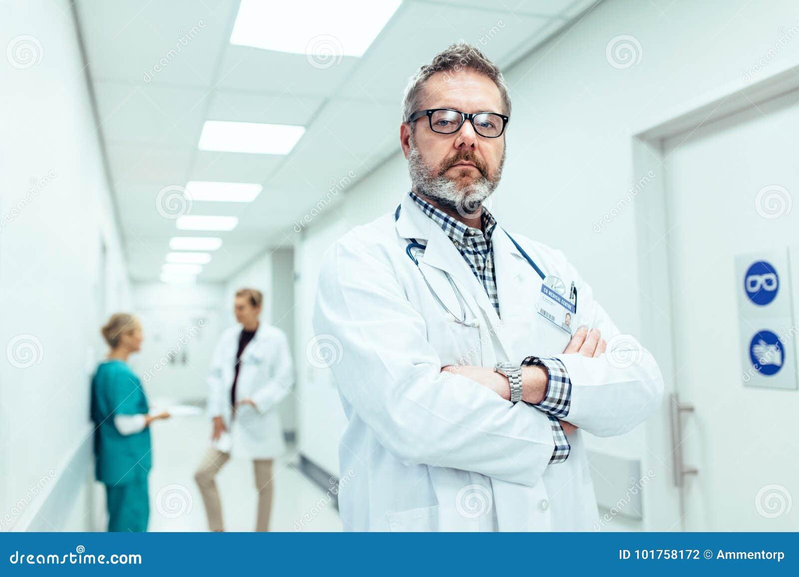 Experienced doctor standing in hospital corridor