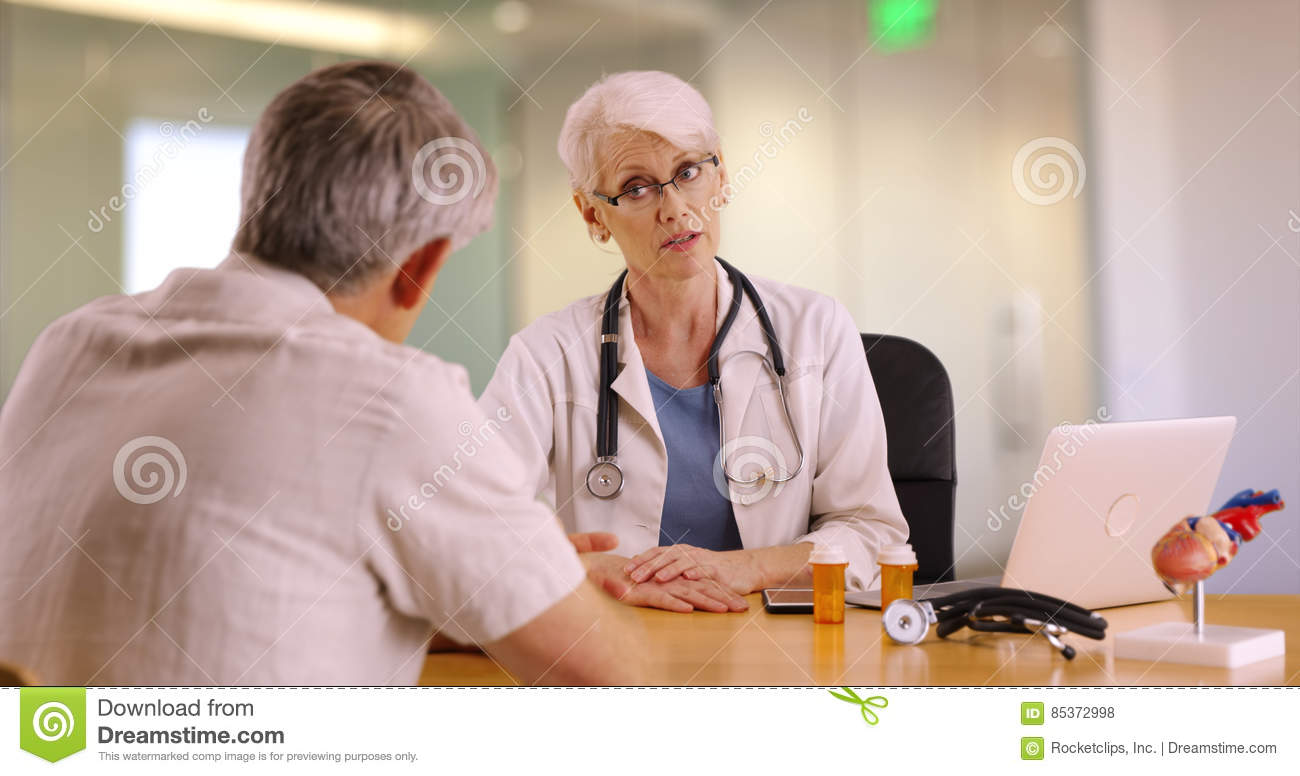 Experienced doctor talking with elderly man in the office