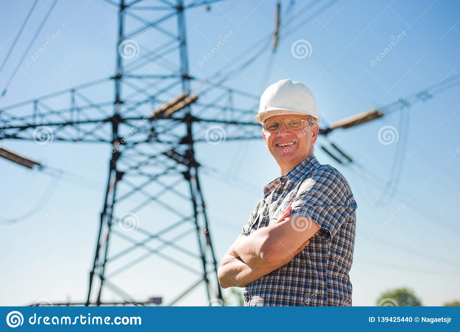 Experienced engineer with white hard hat under the power lines.