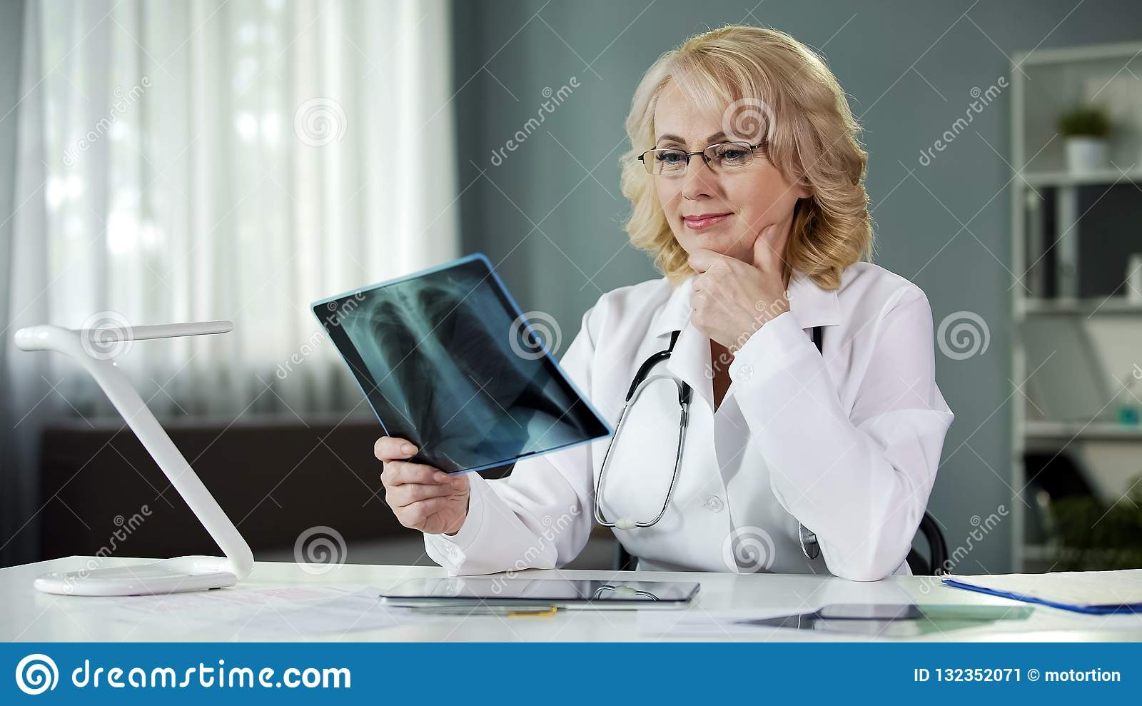 Experienced female radiologist studying X-ray picture, qualified diagnostics