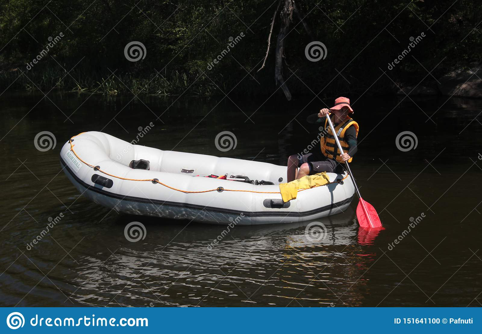 Experienced guide swims on a white raft alone on the river. Rafting at Southern Bug river