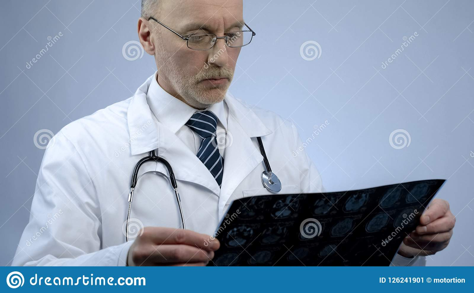 Experienced male therapist looking at patients brain scan, checking MRI results