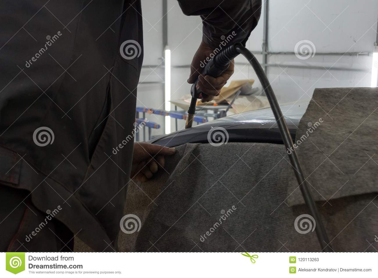 Experienced man performs work on body repair car with a welding machine.