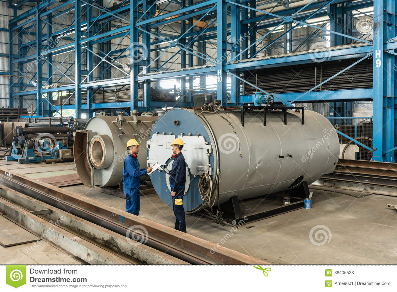 Experienced worker checking the quality of manufactured boilers