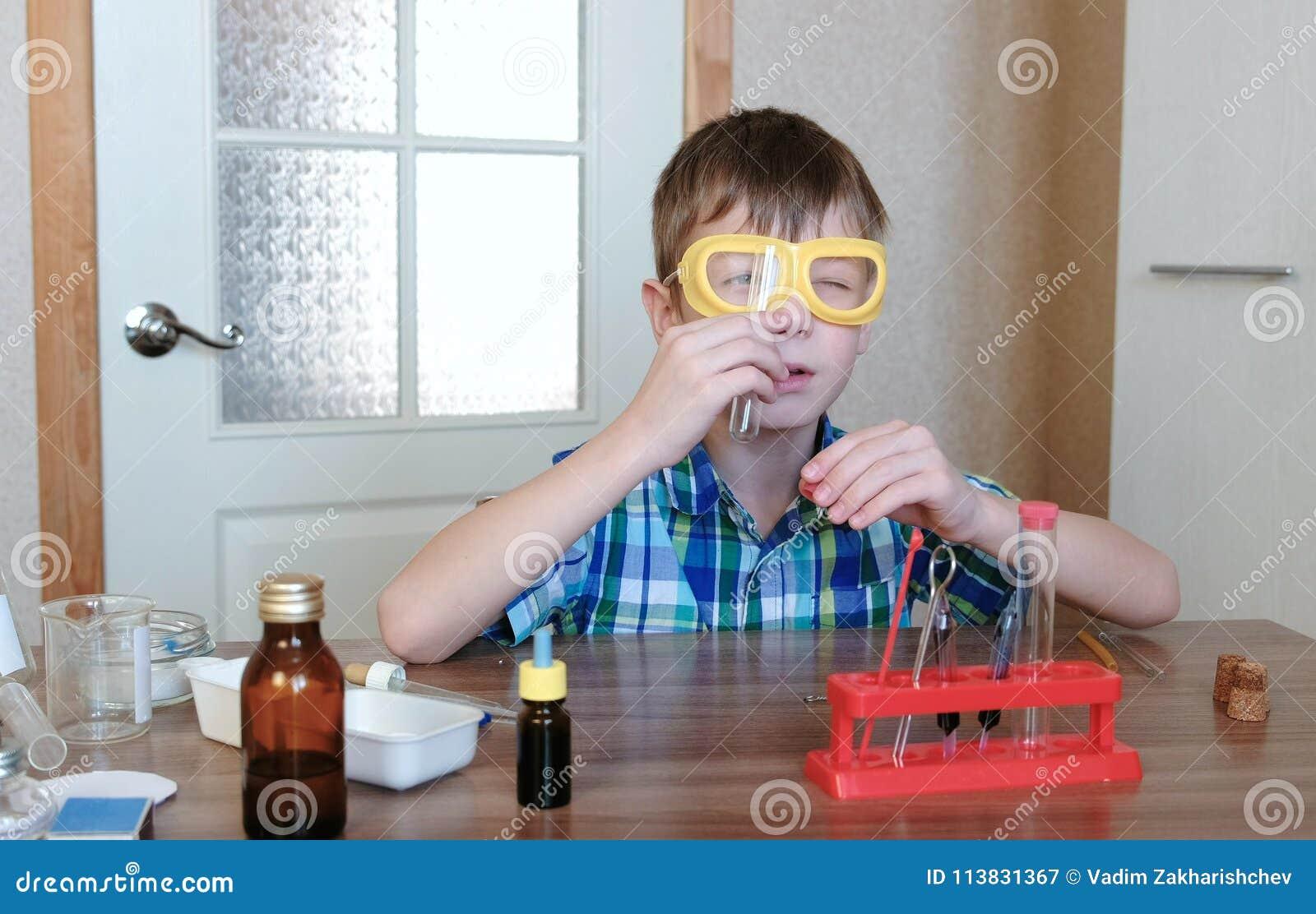 Experimenten op chemie thuis De jongen bekijkt buis om het ervoor te zorgen schone ` s