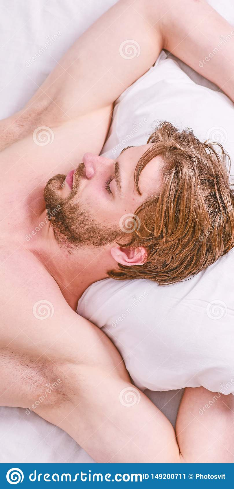 Expert tips on sleeping better. Bearded man sleeping face relaxing on pillow. How much sleep you actually need. Man