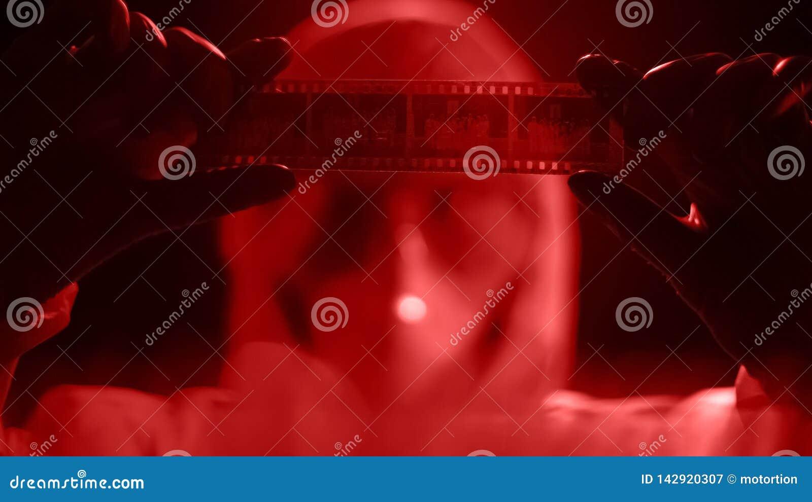 Experto de la ciencia forense que mira las negativas de la foto, buscando para la solución del crimen