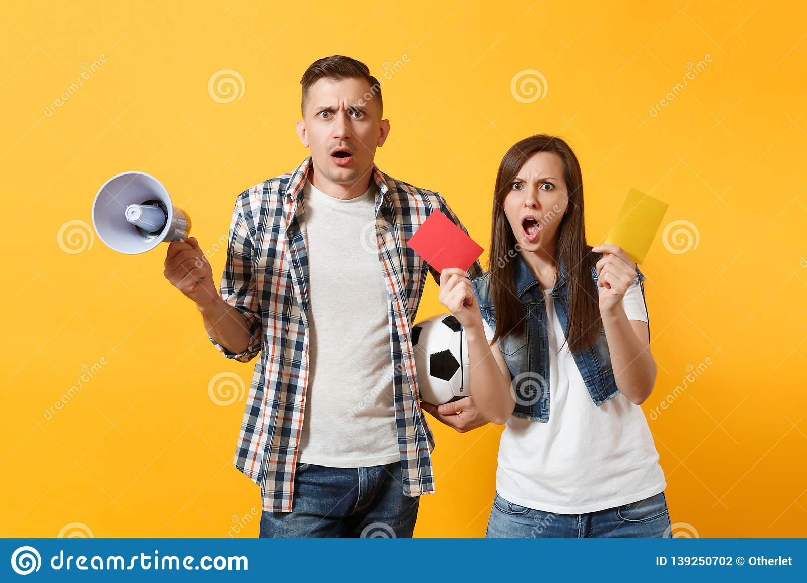 Expessive fun crazy couple, woman man football fans screaming, upset of loss, goal of favorite team with soccer ball