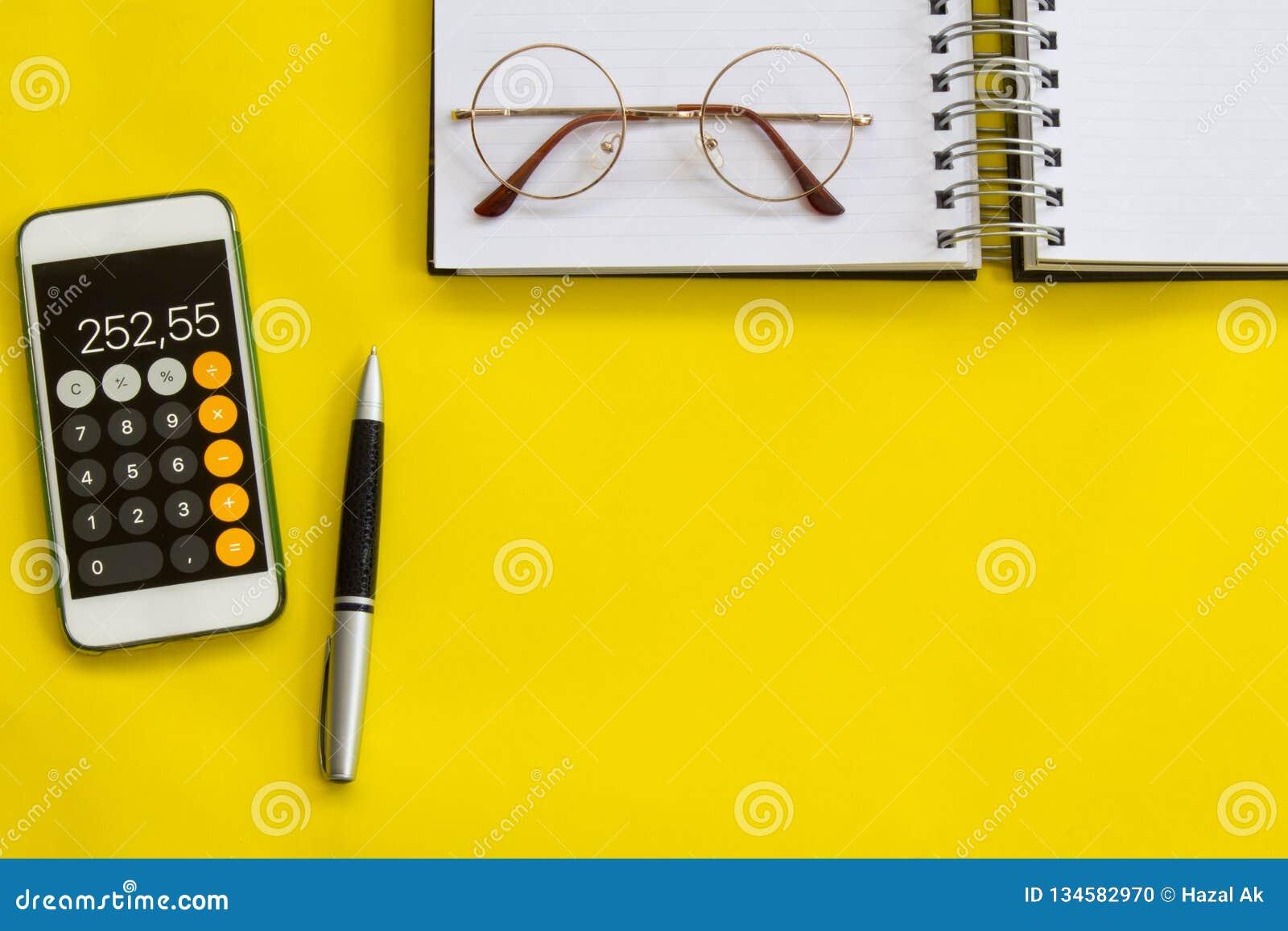 Explicar, conceito financeiro, vista colocada ou superior lisa da pena, telefone esperto com a calculadora com o bloco de notas b