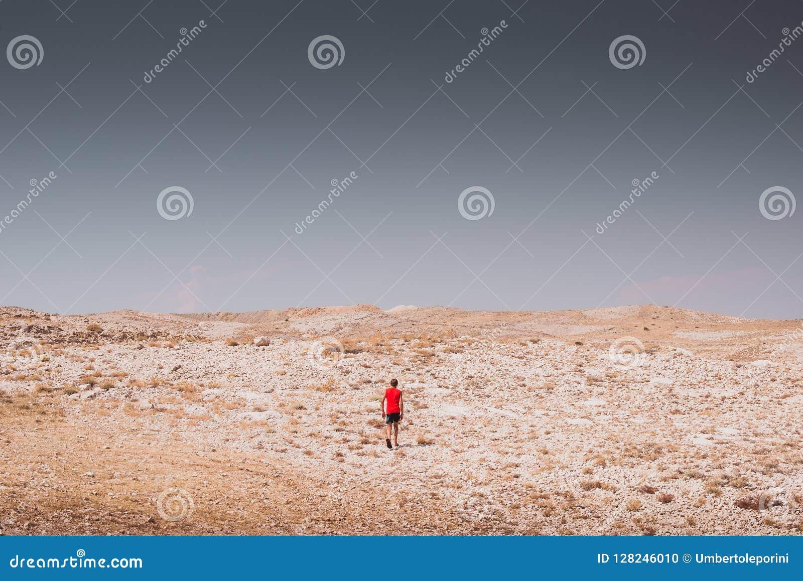 Exploração - menino só que anda em conceitos de uma liberdade rochosa do deserto e do estilo de vida e do esporte da aventura