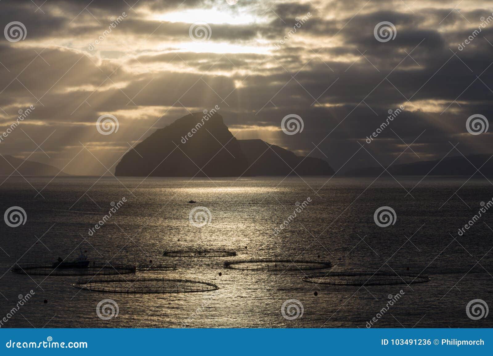 Explorações agrícolas Salmon com céu dramático, Ilhas Faroé