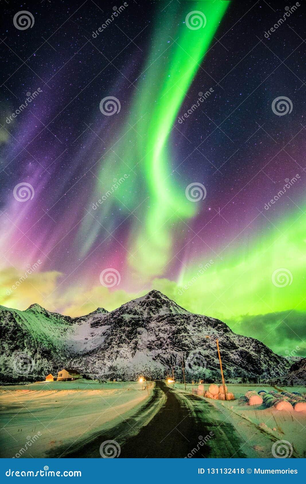 Explosão de Aurora Borealis (aurora boreal) sobre montanhas e r