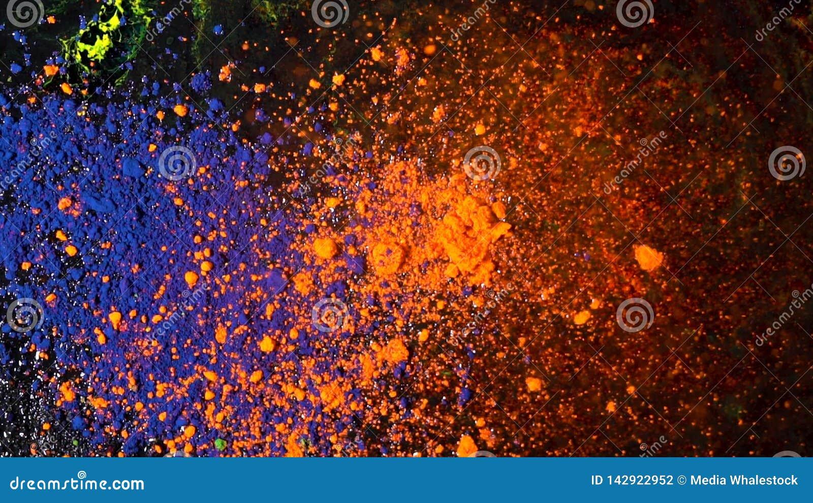 Explosão de poeira colorida brilhante em um fundo preto, conceito da arte Movimento de tintas azuis e alaranjadas do pó, colorido