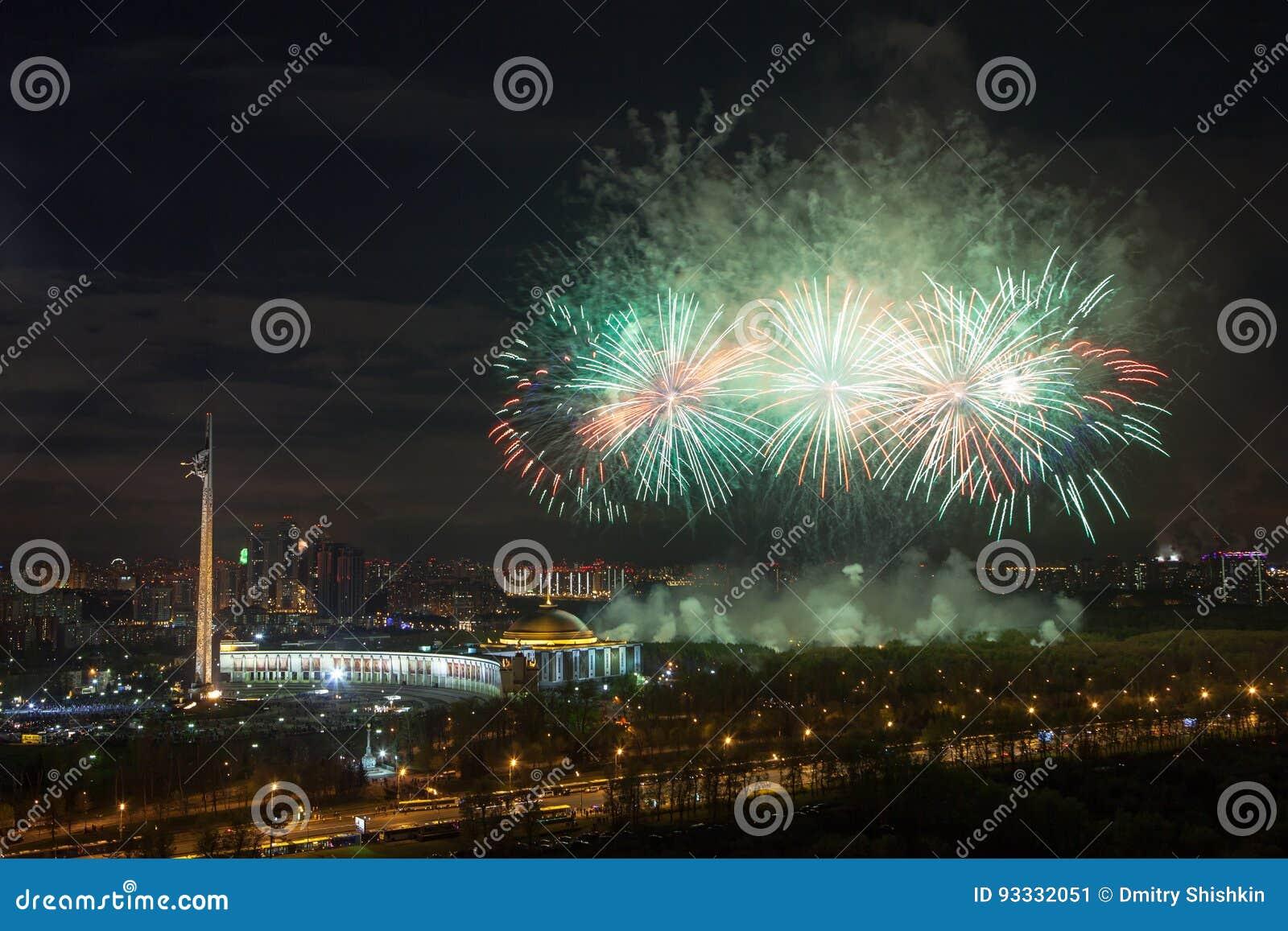 Explosiones brillantes de los fuegos artificiales en cielo nocturno en Moscú, Rusia