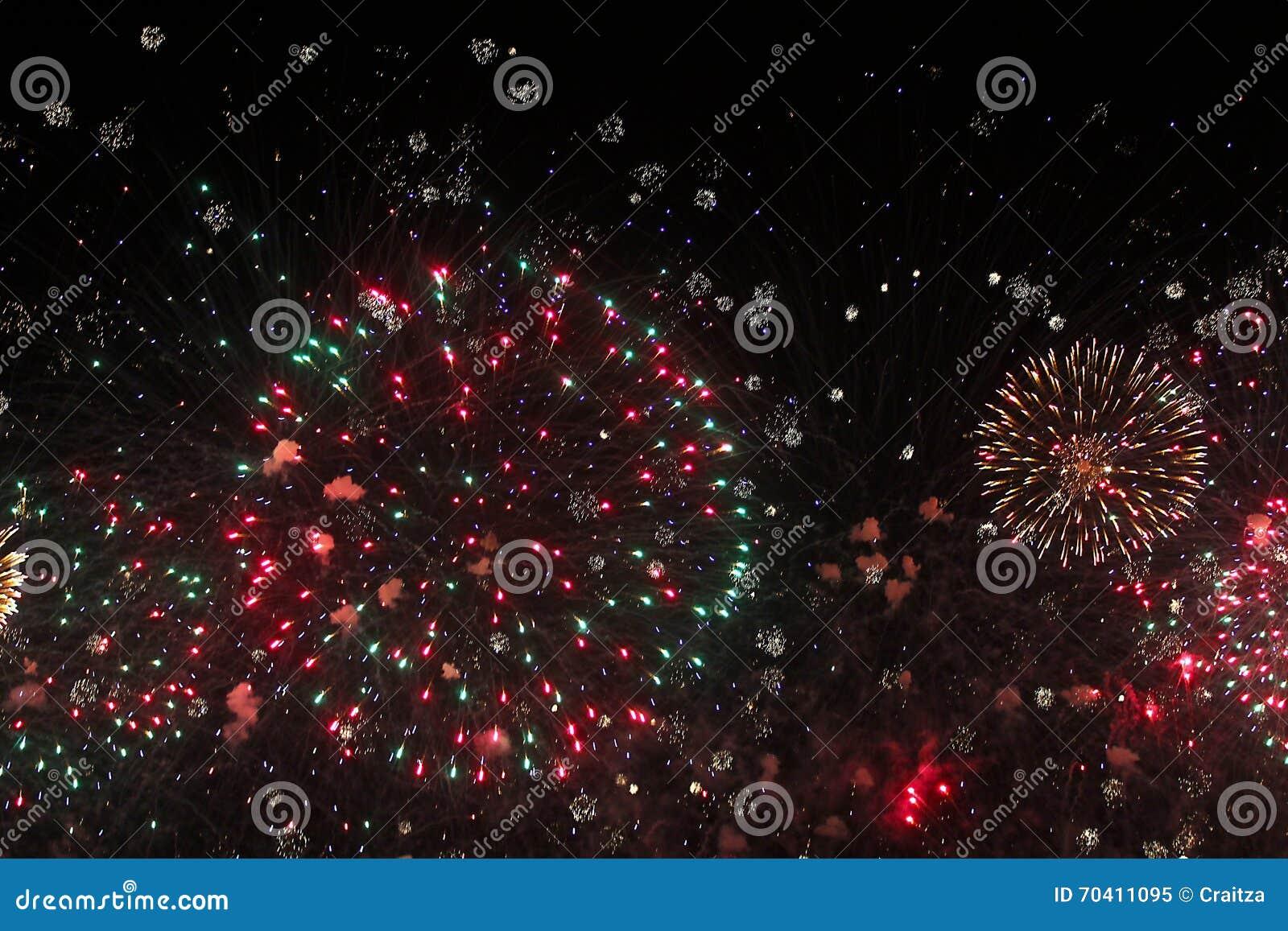 Explosiones rojas y verdes de los fuegos artificiales de la Navidad
