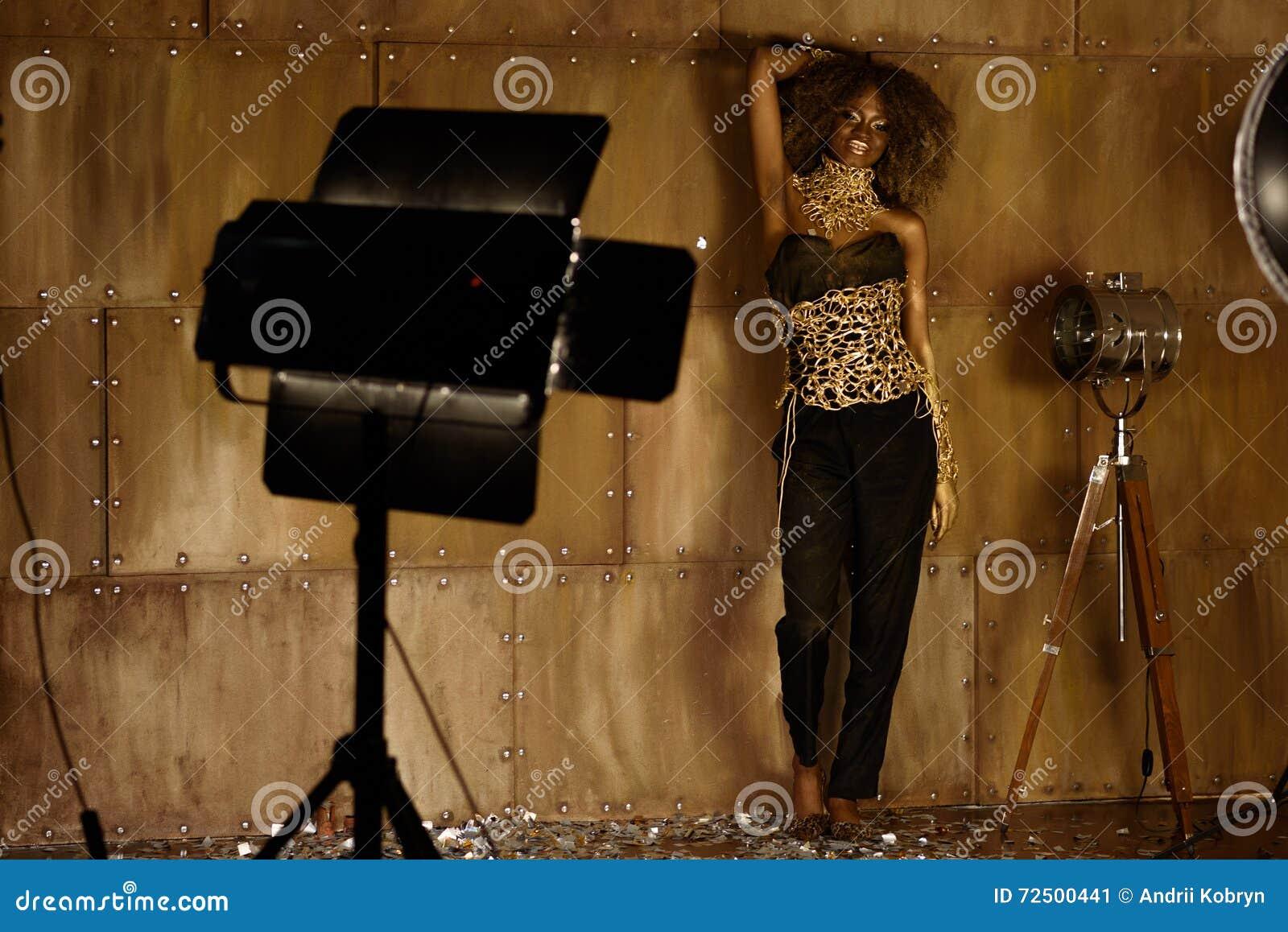 Exponerar den kvinnliga modellen för den eleganta afrikanska amerikanen i guld- tillbehör som står och poserar nära studioljus