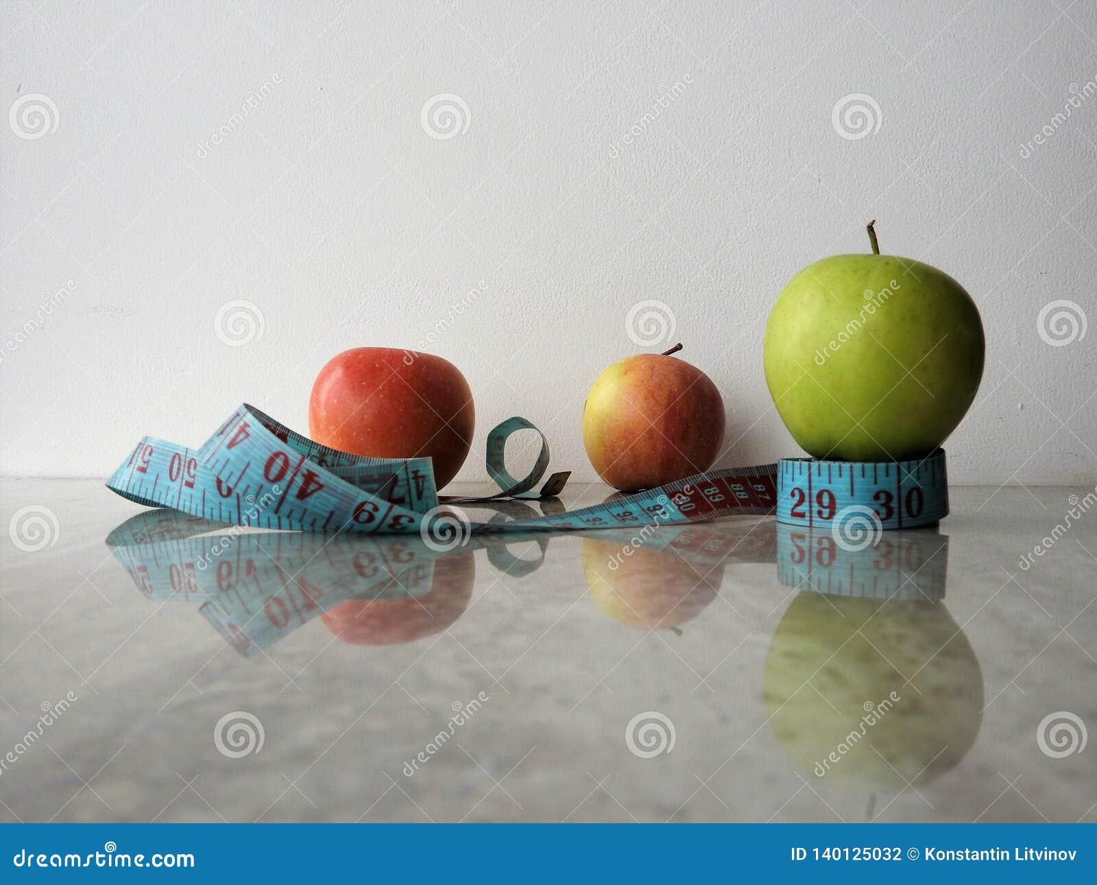 Exponeringsglas av äppleyoghurtdrinken, grönt äpple, anteckningsbok, blyertspenna och mätaband