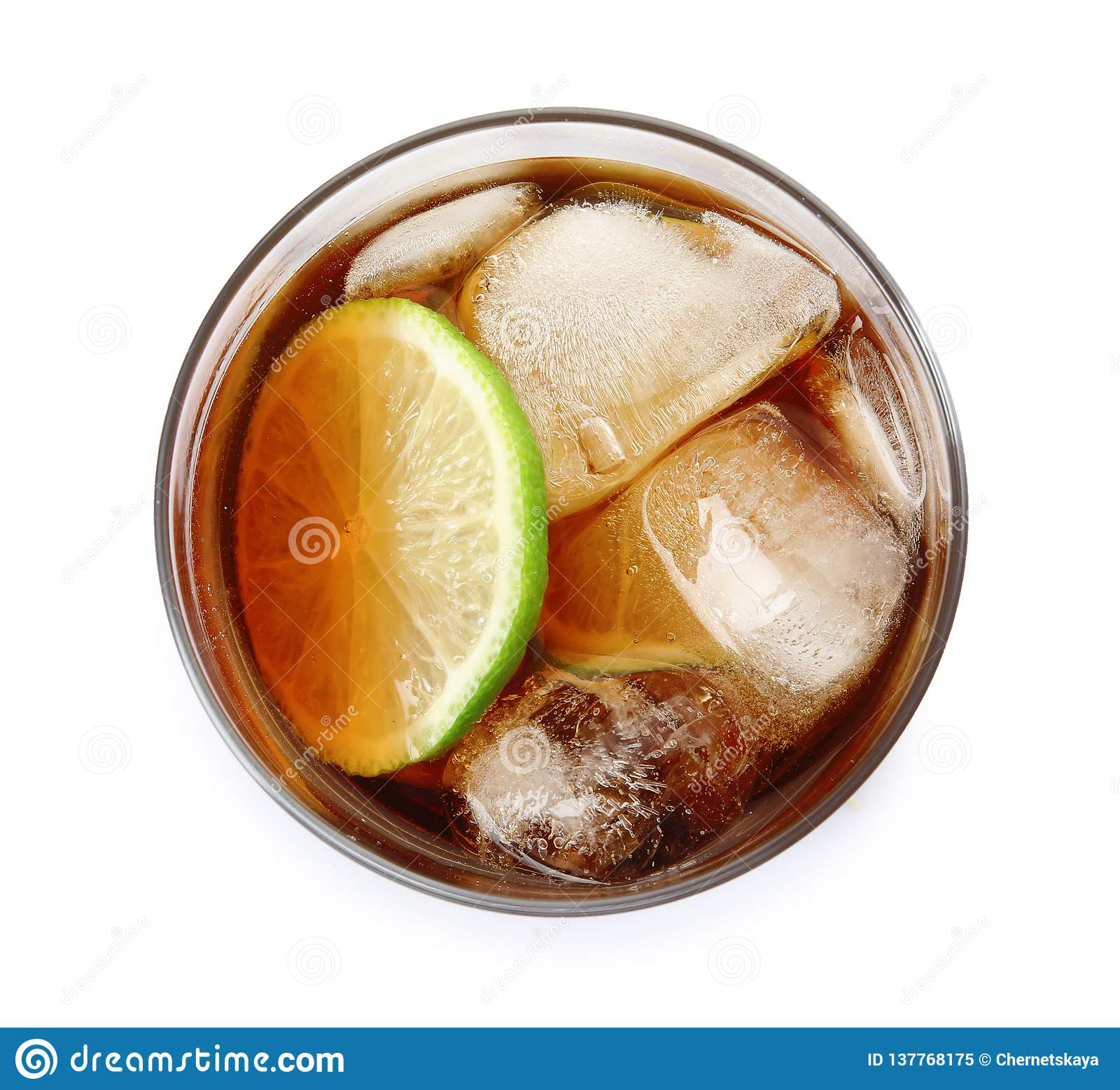 Exponeringsglas av coctailen med cola, is och klippt limefrukt på den vita bästa sikten