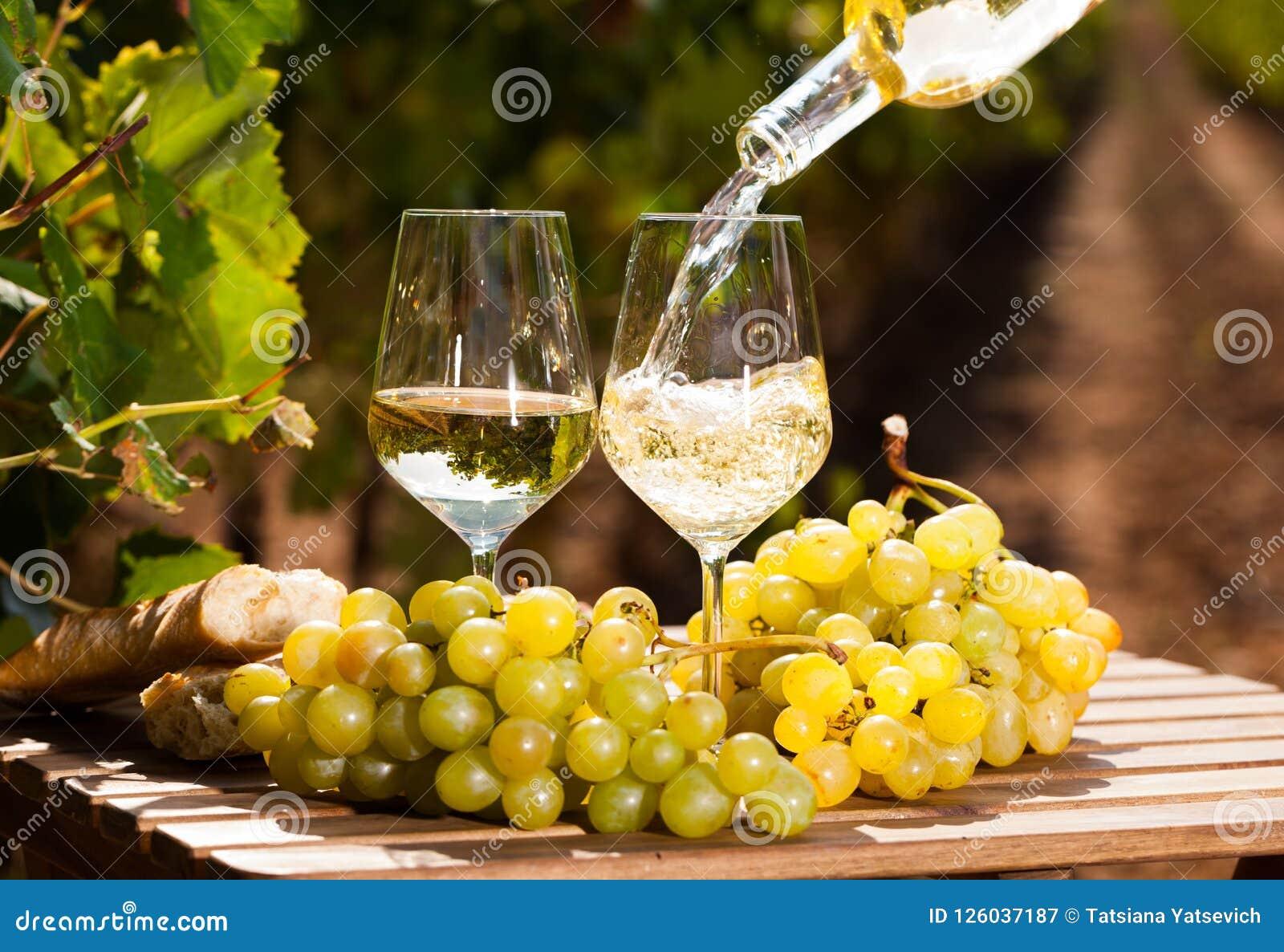 Exponeringsglas av druvor och bröd för vitt vin mogna på tabellen i vingård