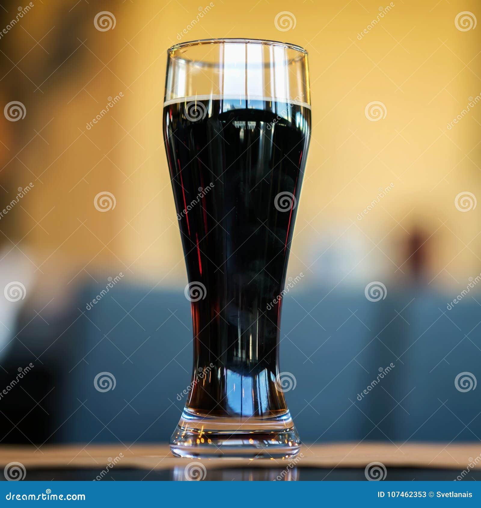 Exponeringsglas av mörkt öl i stång eller i barslut upp Verklig plats Begrepp av ölkultur, hantverkbryggeriet, festivaler och möt