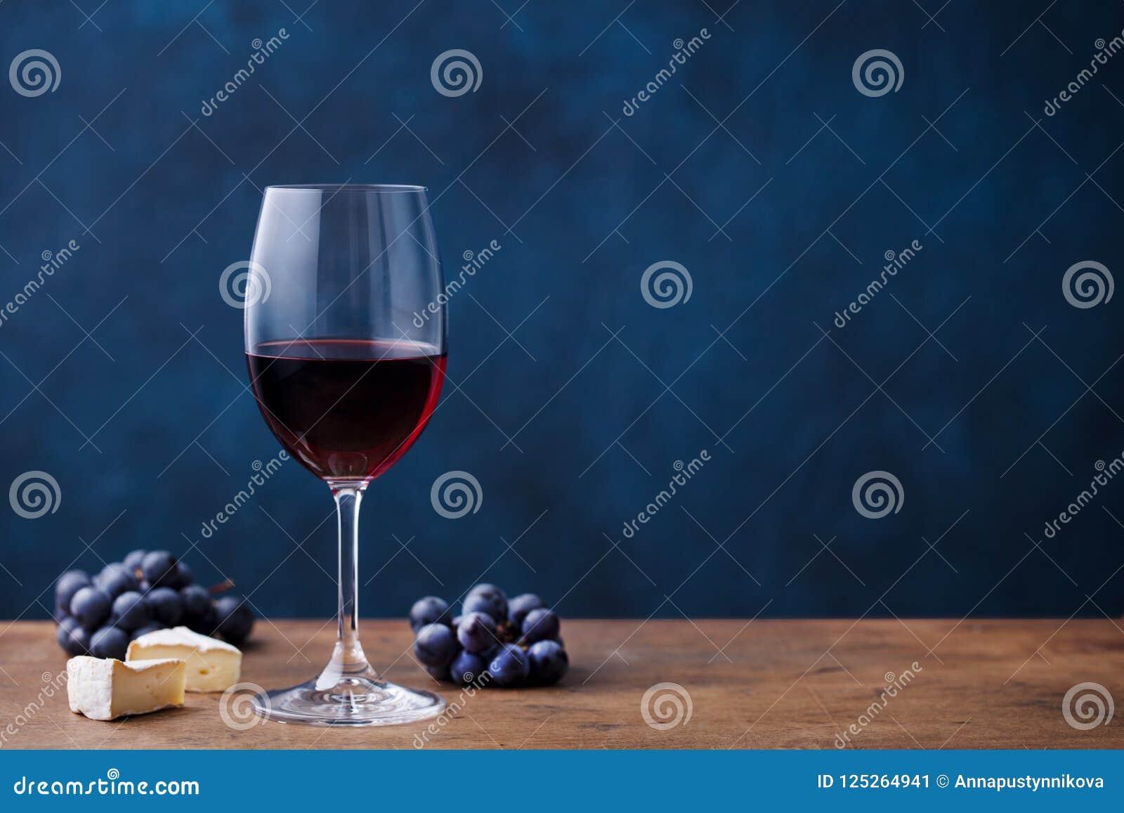 Exponeringsglas av rött vin med den ny druvan och ost på trätabellen background card congratulation invitation kopiera avstånd