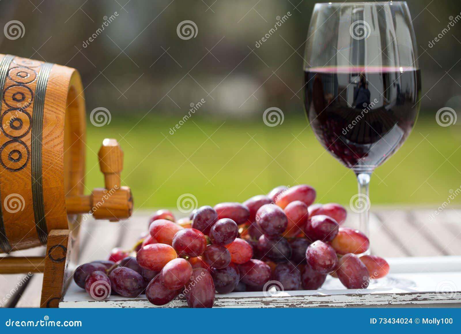 Exponeringsglas av rött vin med druvor på trätabellen