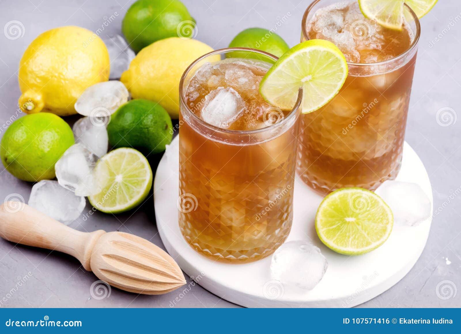 Exponeringsglas av Tsasty iste med iskuber och träpress för citrus förkylningSumm-hm dryck och rå citroner och limefrukter på bak