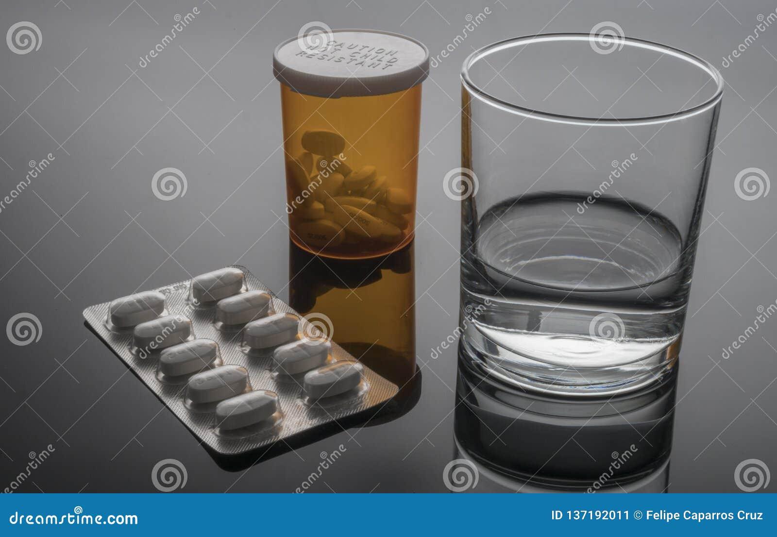 Exponeringsglas av vatten bredvid blåsapacke av piller