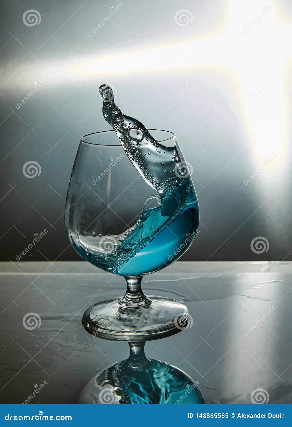 Exponeringsglas av vatten med en v?g p? en gr? bakgrund