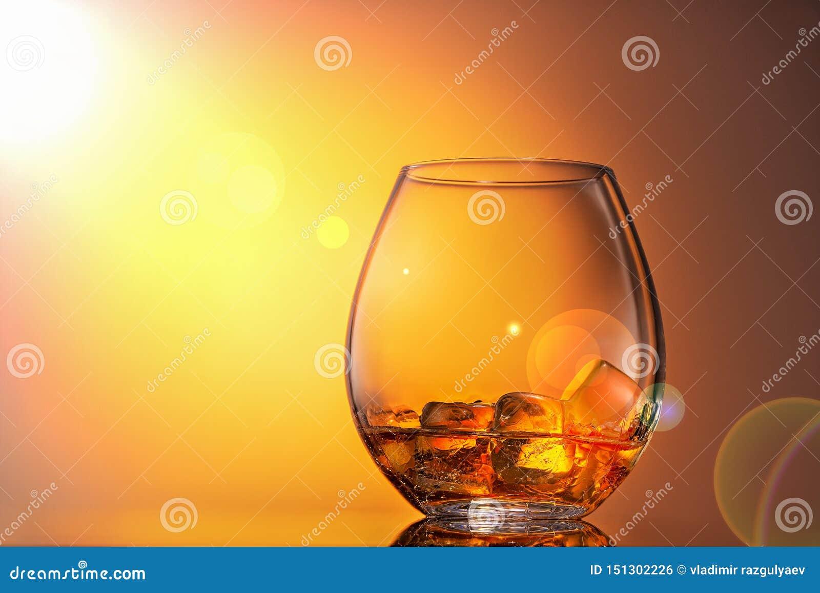 Exponeringsglas av whiskyskotsk whisky med is på en orange bakgrund, exponeras det av solljus Slut upp, kopieringsutrymme