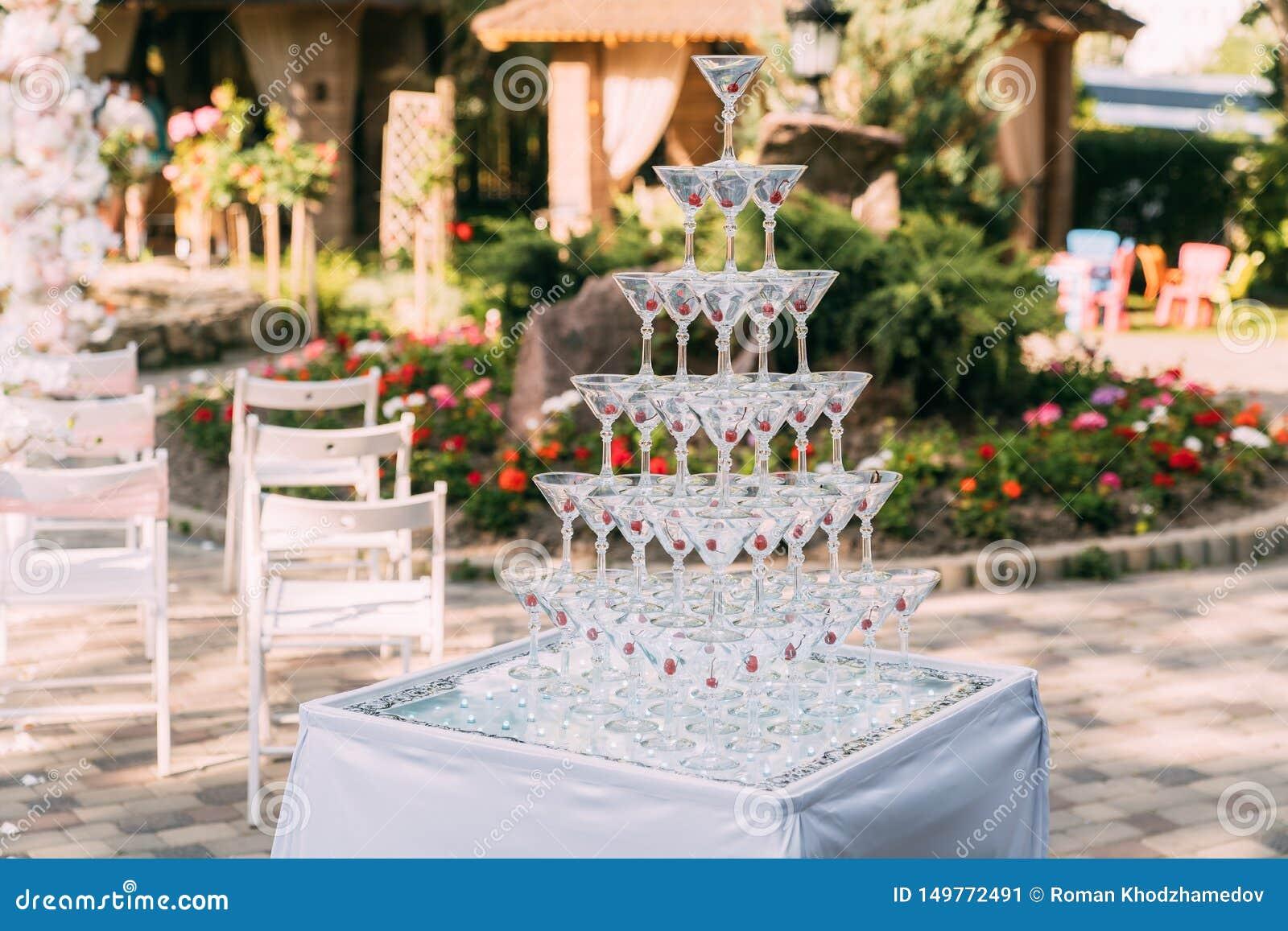 Exponeringsglas f?r alkoholdrycker Pyramid som göras av champagneexponeringsglas med körsbäret