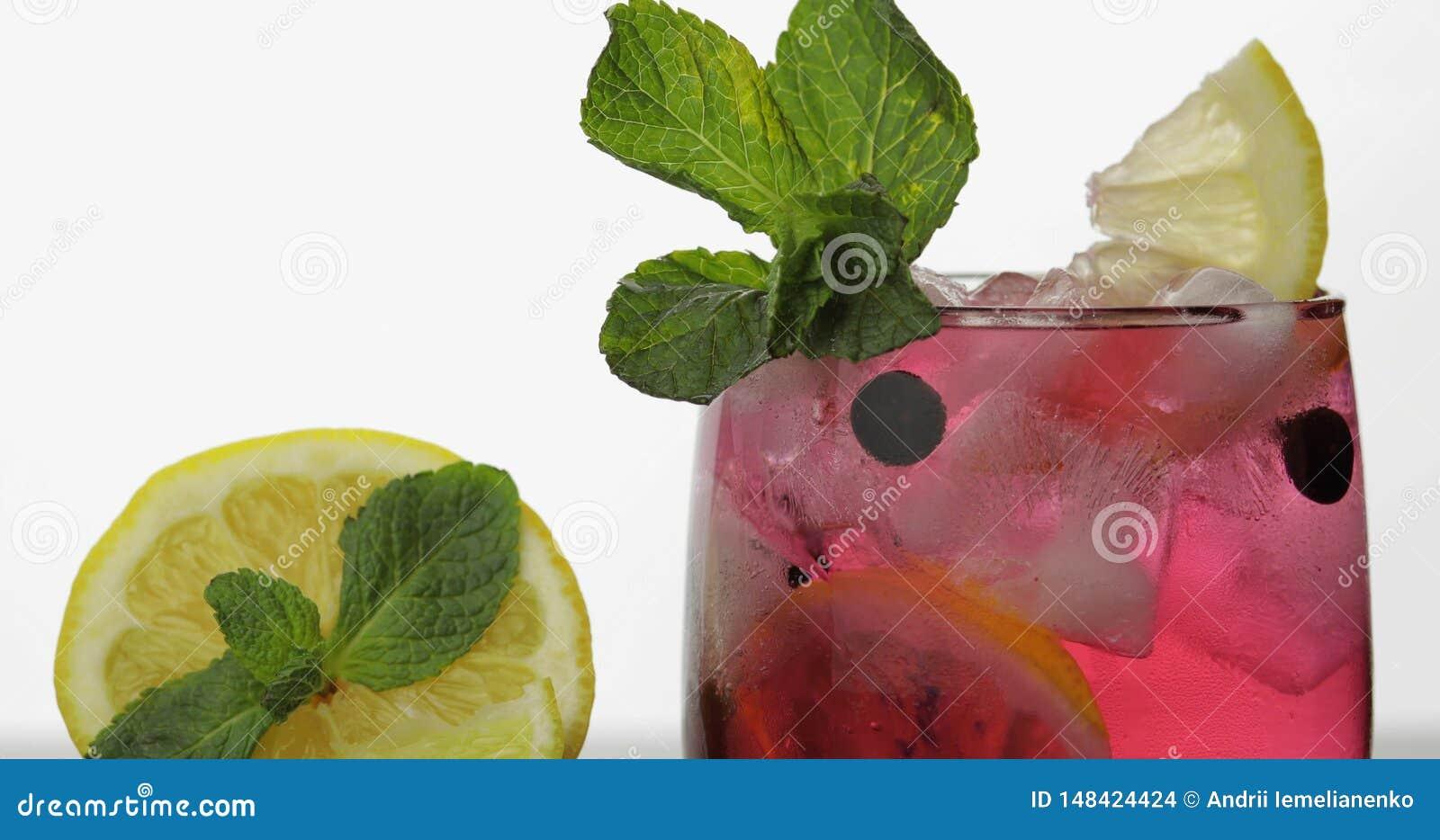 Exponeringsglas med den kalla röda drinken med sidor av mintkaramellen, citronen, svarta vinbär och is